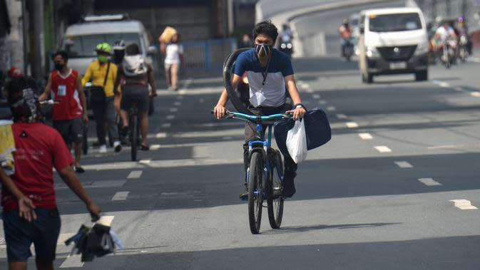 Seorang pria mengendarai sepedanya untuk bekerja di Manila pada 20 Mei 2020. Penjualan sepeda meroket menyentuh 300-500 unit dalam dua hari sejak pemerintah Filipina mulai melonggarkan langkah-langkah karantina yang dilakukan untuk mencegah penyebaran pandemi COVID-19. (Ted ALJIBE/AFP)