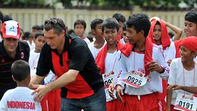 Mantan striker AC Milan Daniele Massaro (kanan) bersama Presiden Direktur PT. ASD Alan Solowiejczyk (kiri) menyalami anak-anak yang mengikuti seleksi beasiswa Milan Junior Camp Bali 2011. (Antara).