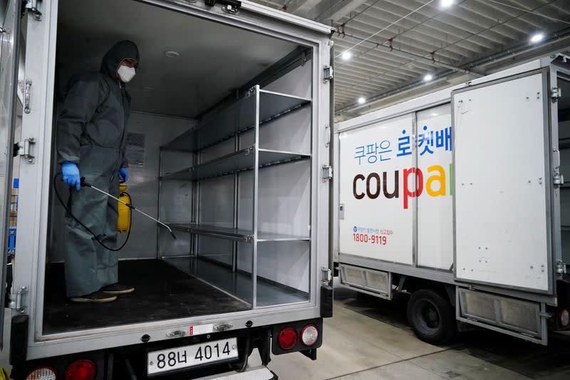 A worker in a protective gear sanitizes a vehicle before leaving to deliver packages in Incheon