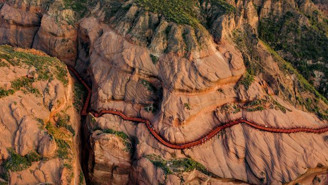 Foto dari udara yang diabadikan pada 24 September 2020 ini memperlihatkan wisatawan tengah mengunjungi kawasan wisata bentuk lahan (landform) Danxia di Kota Longzhou, Wilayah Jingbian, Provinsi Shaanxi, China barat laut. (Xinhua/Tao Ming)