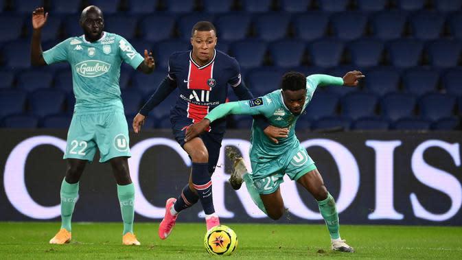 Penyerang PSG, Kylian Mbappe, berusaha melewati pemain Angers pada laga lanjutan Liga Prancis di Parc des Princes Stadium, Sabtu (3/10/2020) dini hari WIB. PSG menang 6-1 atas Angers. (AFP/Franck Fife)