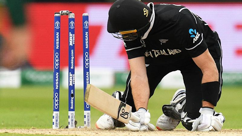 Martin Guptill looks at the stumps after knocking the bails off. (Photo by OLI SCARFF/AFP/Getty Images)