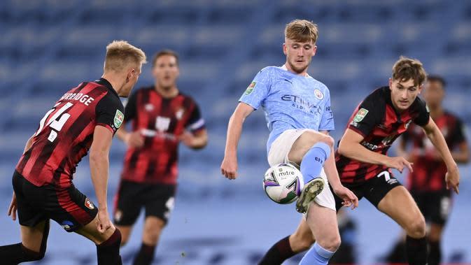Gelandang Manchester City, Tommy Doyle mengontrol bola dari kawalan dua pemain Bournemouth pada pertandingan putaran ketiga Piala Liga Inggris di City of Manchester Stadium di Manchester, Inggris, Kamis (24/9/2020). City menang tipis atas Bournemouth 2-1. (Laurence Griffiths/Pool via AP)