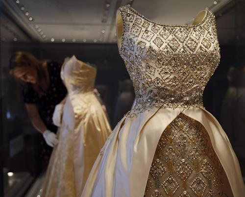 In this photo taken Monday, July 1, 2013, an employee fixes a dress of Queen Elizabeth II on display at the Fashion Rules exhibition at Kensington Palace in London. Opening on 4 July, a new glamorous exhibit at Kensington Palace showcases how the styles of three royal ladies; Queen Elizabeth II, her sometimes risque sister Margaret, and the glamorous Princess Diana, each reflected and influenced the trends of their fashion heyday. (AP Photo/Frank Augstein)