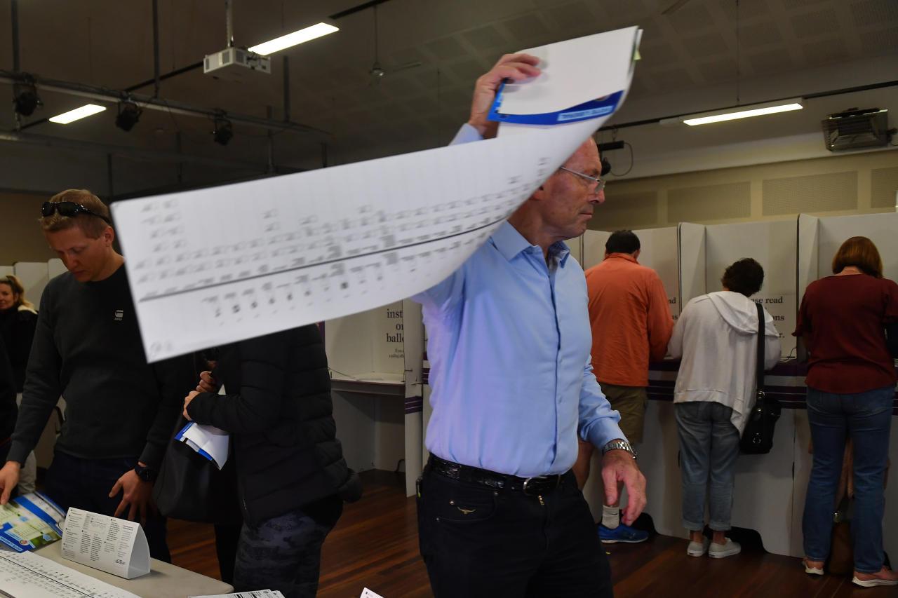 <p>Tony Abbott wrangles the senate ballot paper at Forestville Public School in Sydney. Source: AAP </p>