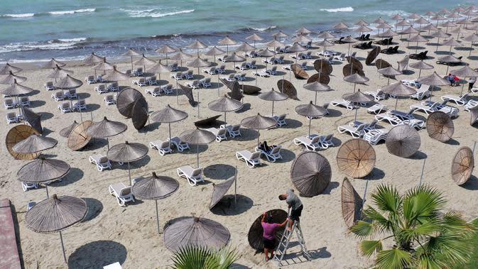 Foto udara pada 1 Juni 2020 menunjukkan para pekerja memasang payung jerami di sebuah pantai di Qerret, dekat kota Kavaja, Albania. Rencananya pada 6 Juni mendatang, semua pantai umum akan dibuka untuk wisatawan setelah Albania menerapkan langkah-langkah pelonggaran pencegahan virus corona. (SHKULLA