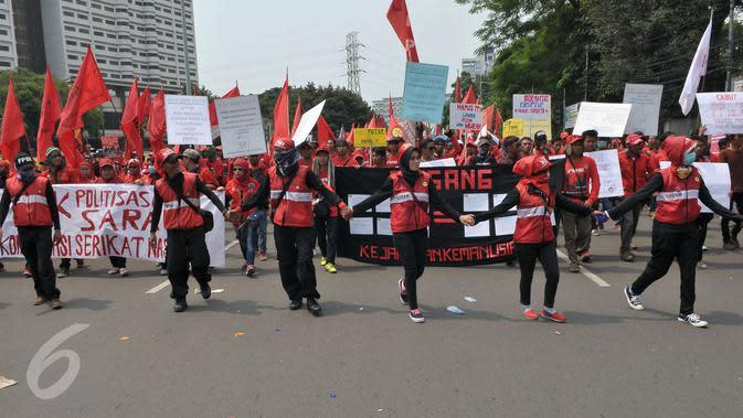 Massa buruh berjalan menuju Istana Negara saat aksi Hari Buruh di Jakarta, Senin (1/5). Dalam aksinya para buruh meminta sistem kerja kontrak dan upah rendah dihapus. (Liputan6.com/Helmi Afandi)