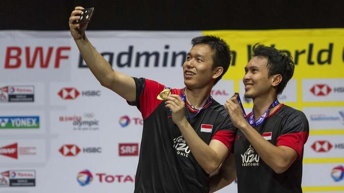 Pasangan Indonesia, Hendra Setiawan/Mohammad Ahsan melakukan swafoto usai menjuarai Kejuaraan Dunia Bulutangkis 2019 setelah mengalahkan wakil Jepang, Takuro Hoki/Yugo Kobayashi, Minggu (25/8). Indonesia menang 25-23, 9-21, 21-15. (AP/Georgios Kefalas)