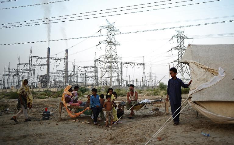 A displaced family sits by its tent in front of DPS thermal power station in Muzaffargah, Punjab province, Pakistan, on September 5, 2010 following floods across the region
