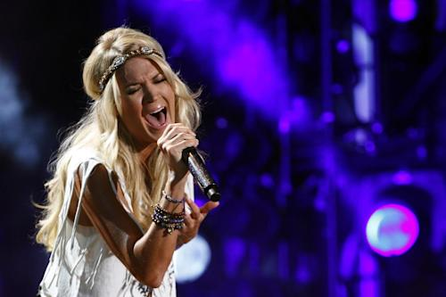 "FILE - This June 9, 2013 file photo shows Carrie Underwood performing at the 2013 CMA Music Festival in Nashville, Tenn. On Sept. 8, Underwood will sing ""Waiting All Day for Sunday Night,"" the new theme song for ""Sunday Night Football."" (Photo by Wade Payne/Invision/AP, File)"
