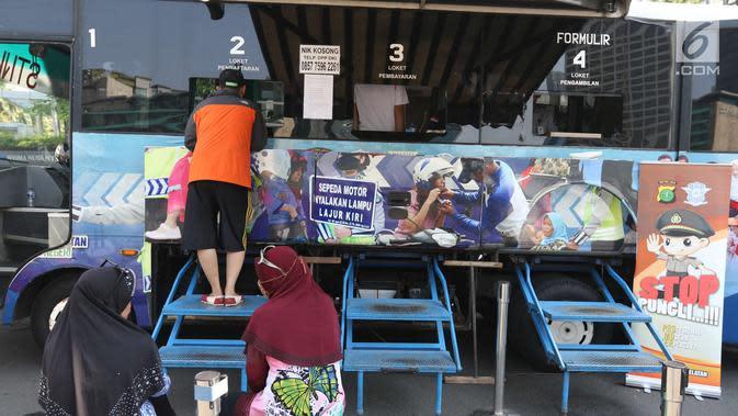Warga membayar pajak kendaraan bermotor di gerai Samsat Keliling Car Free Day, Jakarta, Minggu (21/10). Agar bisa membayar pajak ini cukup menggunakan STNK dengan nama yang tertera harus sesuai KTP. (Liputan6.com/Angga Yuniar)