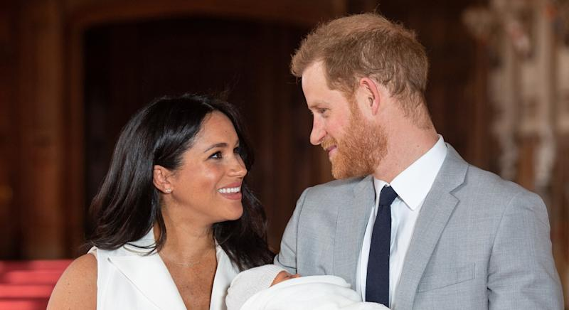 Prince Harry and Meghan Markle smile at each other while Harry holds baby Archie