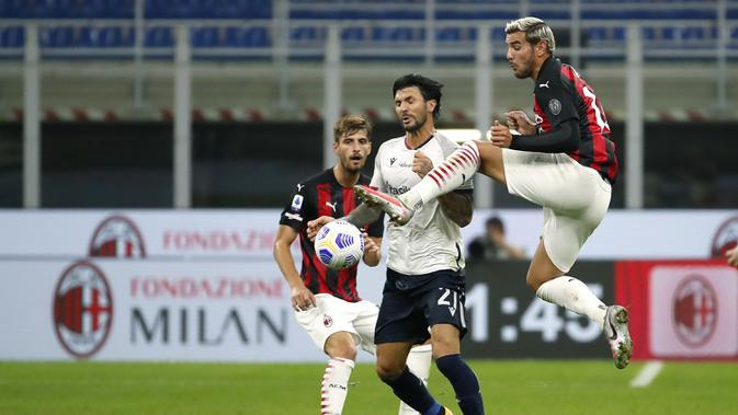 Pemain AC Milan Theo Hernandez (kanan) berebut bola udara dengan pemain Bologna Roberto Soriano pada pertandingan Serie A di Stadion San Siro, Milan, Italia, Senin (21/9/2020). AC Milan menaklukkan Bologna 2-0. (AP Photo/Antonio Calanni)