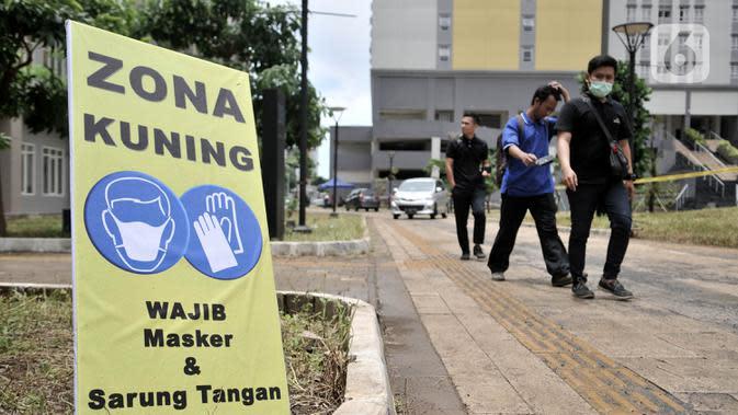Pejalan kaki melintasi tanda zona kuning di Rumah Sakit Darurat Penanganan COVID-19 di Wisma Atlet, Kemayoran, Jakarta, Minggu (22/3/2019). RS Darurat Penanganan COVID-19 siap dioperasikan besok. (merdeka.com/Iqbal S. Nugroho)