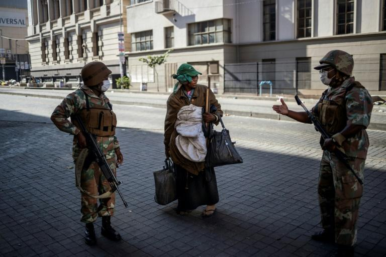 Troops escorted a homeless woman in Johannesburg to a gathering point