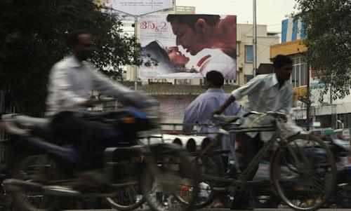 "Indian commuters move past a poster of Bollywood film ""Jism 2"" in Hyderabad, India, Thursday, Aug. 2, 2012. ""Jism 2"" stars a hard-core porn actress, and it does have that pesky title. But it's not a porn movie. Bollywood is certainly not ready for that. The film, which will be released across India on Friday, is pushing the ever-widening sexual boundaries enjoyed by many in urban India. (AP Photo/Mahesh Kumar A.)"