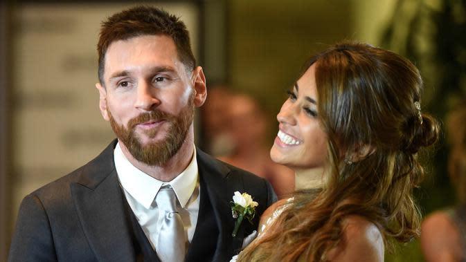 Bintang Barcelona, Lionel Messi bersama istrinya, Antonella Roccuzzo, tampak mesra usai acara pernikahannya di Rosario, Argentina, (30/6/2017). (AFP/Eitan Abramovich)