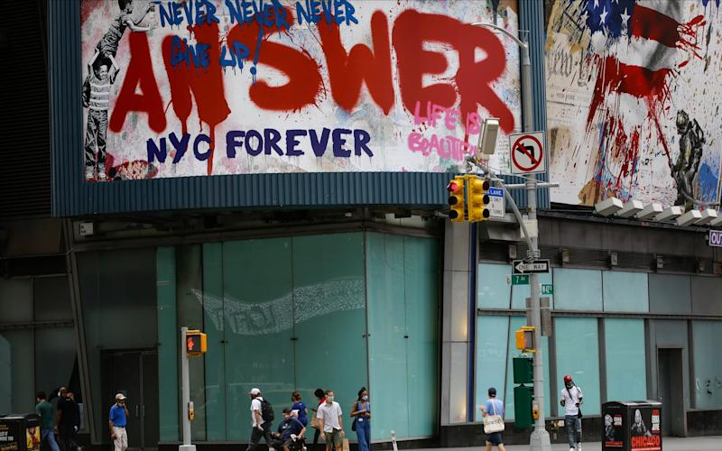 Pedestrians wear protective masks as they walk around New York - AP Photo/Frank Franklin II