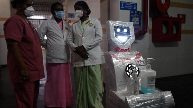 Staf medis berpartisipasi dalam demo robot interaktif 'Zafi' di rumah sakit Stanley Medical di Chennai, 6 April 2020. Rumah sakit ini mengerahkan robot untuk melayani makanan dan obat-obatan bagi pasien Covid-19 dalam upaya meminimalkan tenaga medis tertular virus corona. (Arun SANKAR/AFP)