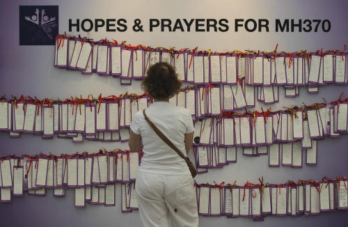 A woman read message cards tied up for passengers aboard a missing Malaysia Airlines plane, at a shopping mall in Kuala Lumpur, Malaysia, Monday, March 24, 2014. A Chinese plane on Monday spotted two white, square-shaped objects in an area identified by satellite imagery as containing possible debris from the missing Malaysian airliner, while the United States separately prepared to send a specialized device that can locate black boxes. (AP Photo)