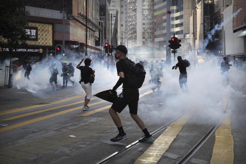 FILE - In this Saturday, Nov. 2, 2019, file photo, pro-democracy protesters react as police fire tear gas during a protest in Hong Kong. By day, the small commercial kitchen in a Hong Kong industrial building produces snacks. At night, it turns into a secret laboratory assembling a detox kit to help frontline pro-democracy protesters counter ill-effects from repeated exposure to tear gas. (AP Photo/Kin Cheung, File)