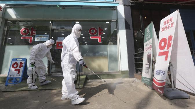 Pekerja mendisinfeksi halaman apotek di Goyang, Korea Selatan, Selasa (25/8/2020). Korea Selatan menutup sekolah dan beralih kembali ke pembelajaran jarak jauh setelah memasuki hari ke-12 peningkatan berturut-turut dalam kasus COVID-19. (AP Photo/Ahn Young-joon)