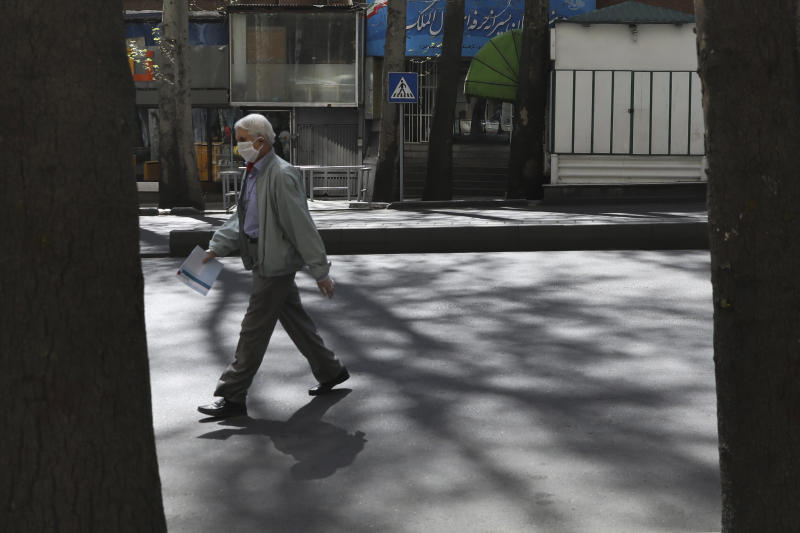 A man wearing a face mask and gloves to protect against the new coronavirus crosses the street in northern Tehran, Iran, Saturday, April 4, 2020. In the first working day after Iranian New Year holidays authorities have allowed some government offices and businesses to re-open with limited working hours, when schools, universities, and many businesses still are ordered to be closed aimed to prevent the spread of the virus.  (AP Photo/Vahid Salemi)