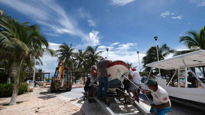 Sejumlah orang memindahkan sebuah perahu saat Badai Delta mendekati Puerto Morelos, Negara Bagian Quintana Roo, Meksiko, 6 Oktober 2020. Status Badai Delta naik menjadi topan tropis kategori 4 pada Selasa (6/10) pagi waktu setempat ketika bergerak menuju Mexican Caribbean. (Xinhua/Israel Rosas)
