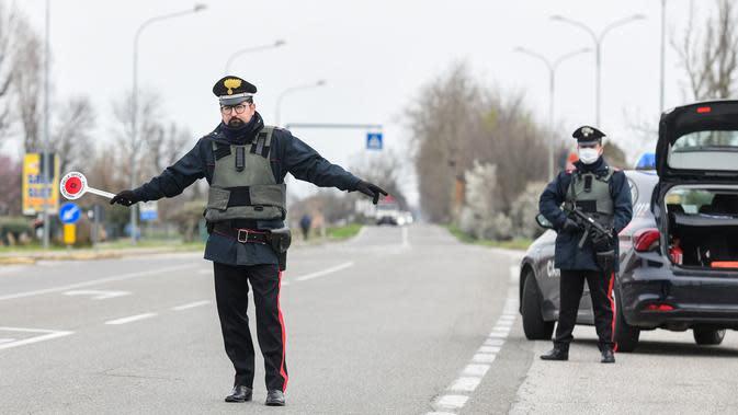 Polisi menjaga perbatasan Modena dan Bologna di Valsamoggia, Bologna, Italia, Senin (9/3/2020). Sebelumnya, pemerintah Italia hanya menutup wilayah utara negaranya untuk menekan penyebaran virus corona (COVID-19). (Piero CRUCIATTI/AFP)