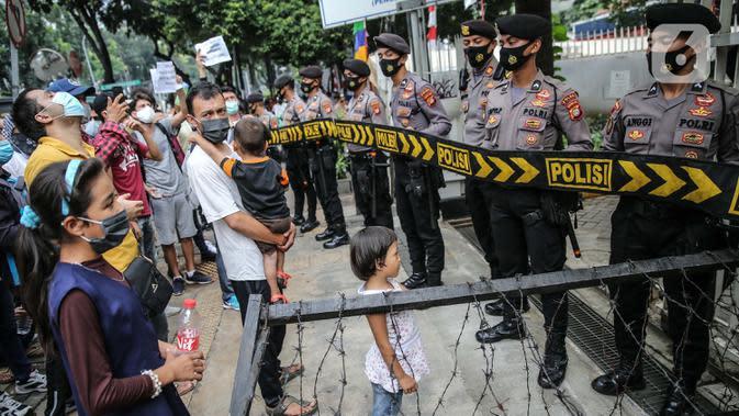 Petugas kepolisian berjaga saat demo para pencari suaka di depan kantor UNHCR, Jakarta, Selasa (18/8/2020). Dalam aksinya mereka meminta pertanggung jawaban dari UNHCR karena hingga saat ini banyak para pencari suaka tidak mendapatkan kejelasan akan nasibnya di Indonesia. (Liputan6.com/Faizal Fanani