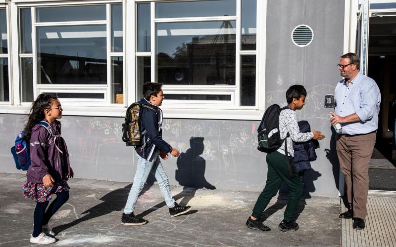 A Danish headteacher hands out hand sanitiser to his pupils on arrival at school - Ritzau Scanpix