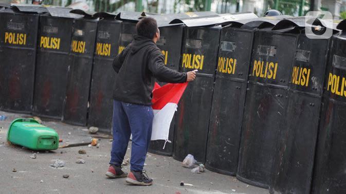 Pengunjuk rasa membawa bendera Merah Putih saat terlibat bentrok dengan polisi di Jalan Medan Merdeka Timur, Jakarta, Kamis (8/10/2020). Bentrokan terjadi akibat massa yang memaksa masuk ke depan Istana Negara untuk berunjuk rasa terkait penolakan UU Cipta Kerja. (Liputan6.com/Immanuel Antonius)