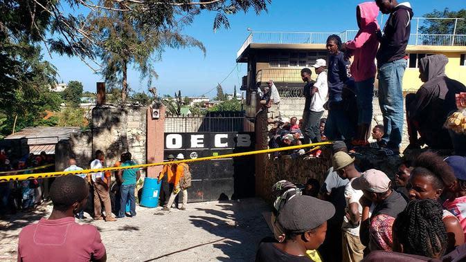 Orang-orang berdiri di luar Panti Asuhan Church of Bible Understanding di mana kebakaran terjadi, menewaskan 13 anak-anak.(Source: Dieu Nalio Chery / AP)