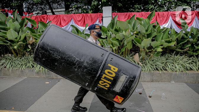 Personel kepolisian dengan membawa tameng bersiap untuk berjaga di sekitar Gedung DPR/MPR RI, Jakarta, Jumat (14/8/2020). Pengamanan ekstra tersebut untuk mengantisipasi rencana unjuk rasa menolak RUU Cipta Kerja yang bertepatan dengan Sidang Tahunan di Gedung DPR. (Liputan6.com/Faizal Fanani)