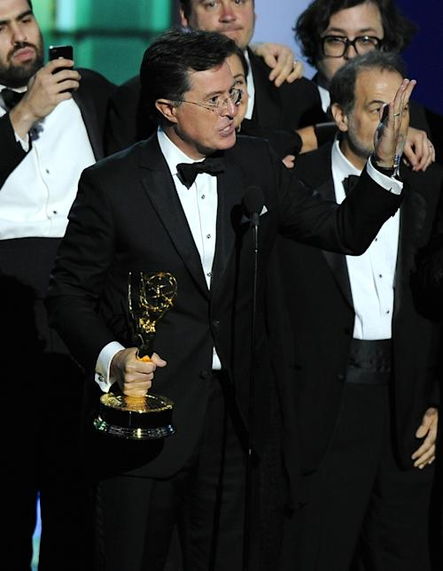 "Stephen Colbert and the cast and crew of ""The Colbert Report"" accept the award for outstanding writing for a variety series at the 65th Primetime Emmy Awards at Nokia Theatre on Sunday Sept. 22, 2013, in Los Angeles. (Photo by Chris Pizzello/Invision/AP)"