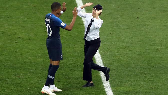 Seorang penyusup melakukan tos dengan pemain timnas Prancis Kylian Mbappe pada laga final Piala Dunia 2018 melawan Kroasia di Luzhniki Stadium, Minggu (15/7). Penyusup masuk ke tengah lapangan saat pertandingan memasuki menit 52. (AP/Thanassis Stavrakis)