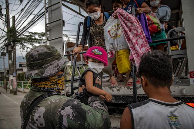 Residents fleeing the eruption arrive to an evacuation center in Santo Thomas on Jan. 13. | Ezra Acayan—Getty Images