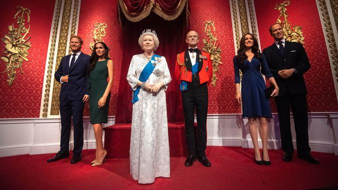 Patung lilin Pangeran Harry dan Meghan Markle berdiri di samping Ratu Elizabeth II, Pangeran Philip, Pangeran William dan Kate Middleton di Madame Tussauds London, Kamis (9/1/2020). Madame Tussauds London menarik replika Harry dan Meghan dari tampilan anggota kerajaan. (Victoria Jones/PA via AP)
