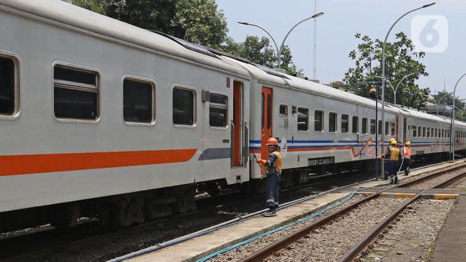 Petugas membersihkan gerbong kereta api di Stasiun Pasar Senen, Jakarta. (Liputan6.com/Herman Zakharia)