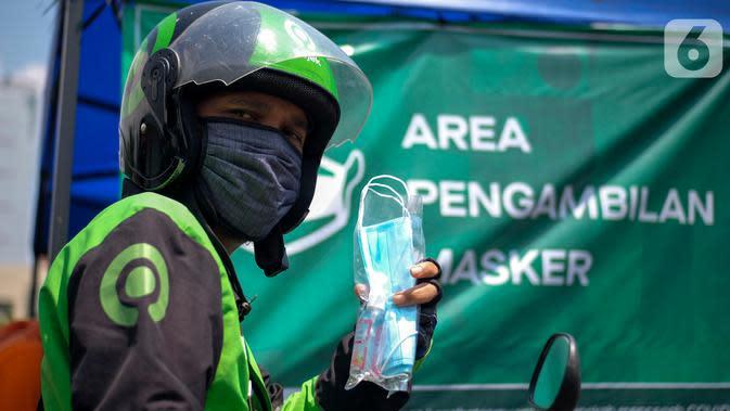 Mitra Gojek saat menerima masker di Posko Aman Bersama Gojek, Kemayoran, Jakarta, Kamis (23/4/2020). Posko Gojek menerapkan drive thru dengan 3 jenis layanan mulai dari pembagian healthy kit, pengecekan suhu tubuh dan penyemprotan cairan disinfektan untuk kendaraan. (Liputan6.com/HO/Ading)
