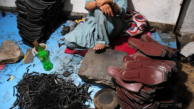 Seorang pembuat sepatu asal Pakistan beristirahat setelah membuat sepatu tradisional yang dikenal sebagai