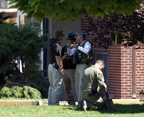 "Federal agents outside the apartment of James Holmes in Aurora, Colo., Saturday, July 21, 2012. Federal authorities detonated one small explosive and disarmed another inside Holmes' apartment, but several other explosive devices remained, said Aurora police Sgt. Cassidee Carlson. Twelve people were killed and dozens were injured in a shooting attack early Friday at a packed movie theater during a showing of the Batman movie, ""The Dark Knight Rises."" Police have identified Holmes, 24, as the suspected shooter. (AP Photo/Ed Andrieski)"