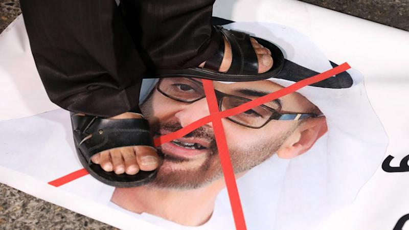A Palestinian protester stands on a photo of Abu Dhabi Crown Prince Mohammed bin Zayed at a protest in Bethlehem against the UAE`s decision to normalise relations with Israel (16 August 2020)