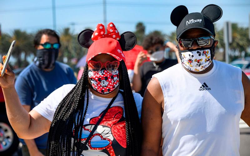 A couple waits in line to enter Downtown Disney in Anaheim, California - ROBYN BECK/AFP