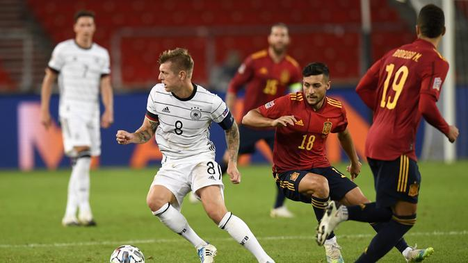 Gelandang Jerman Toni Kroos membawa bola dari kawalan gelandang Spanyol Oscar Rodriguez pada pertandingan UEFA Nations League di Stuttgart, Jerman (3/9/2020). Jerman bermain imbang 1-1 atas Spanyol. (AFP Photo/Thomas Kienzle)