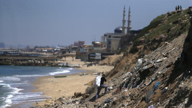 Seorang nelayan membawa hasil tangkapannya selama bulan suci Ramadan di pantai Kota Gaza, Palestina, Jumat (1/5/2020). (MOHAMMED ABED/AFP)