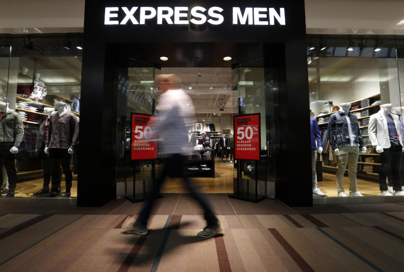A walker passes an Express Men store at the Galleria Mall in Dallas, Wednesday, Jan. 22, 2020. Mall-based clothing chain Express says it plans to close about 100 stores by 2020 as part of an overall strategy to cut $80 million in annual expenses over the next three years. (AP Photo/LM Otero)