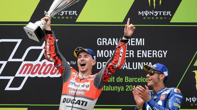 Pembalap Spanyol dari tim Ducati, Jorge Lorenzo merayakan selebrasi didampingi pembalap Italia dari Movistar Yamaha, Valentino Rossi usai balapan MotoGP Catalunya di Sirkuit Catalunya di Montmelo, (17/6). (AFP PHOTO / Lluis Gen)