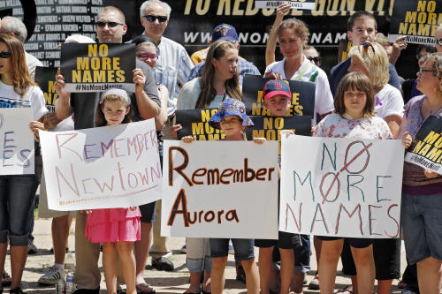 People hold signs as they gather for a remembrance rally for the anniversary of the Aurora theater shooting at Cherry Creek State Park in Aurora, Colo., Friday, July 19, 2013. Saturday, July 20 is the anniversary of the Aurora theater shooting where 12 people were killed and 70 injured. (AP Photo/Ed Andrieski)