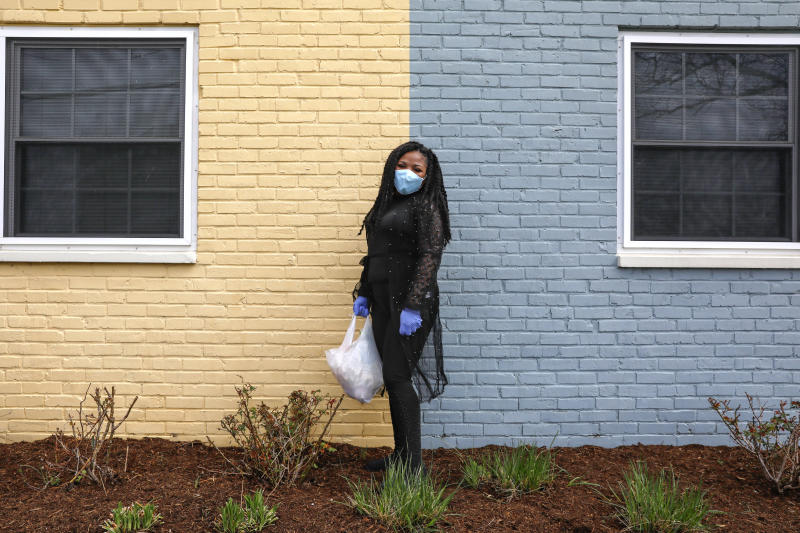In this March 24, 2020, photo, Sharita Creel, of Washington, poses for a portrait holding a donated bag of groceries that she received in her community while wearing a mask and gloves in southeast Washington. Creel received the groceries from a neighborhood food delivery that is part of a new Martha's Table initiative, along with community partners, to get needed food directly to the neighborhoods they serve. Neighborhood volunteers are the tip of the spear for a grassroots community effort to keep Washington's most vulnerable neighborhoods fed during the unprecedented coronavirus crisis which has nearly shut down the American economy. (AP Photo/Jacquelyn Martin)